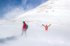 Junge Paare, die in einem geschneiten Berg wandern stockfotografie