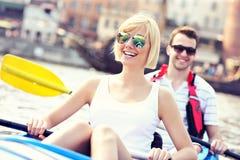Junge Paare, die in einem Kanu sich entspannen Lizenzfreie Stockfotos