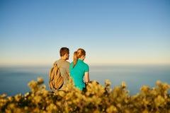 Junge Paare, die in einem Naturreservat mit blauem Himmel sitzen stockbild