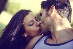 Junge Paare, die in einem schönen Park küssen Lizenzfreie Stockfotos