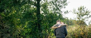 Junge Paare, die in einem Wald umarmen Lizenzfreies Stockbild