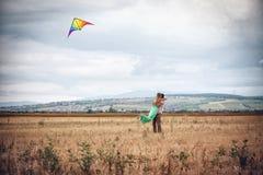Junge Paare, die einen Drachen fliegen Lizenzfreie Stockfotografie