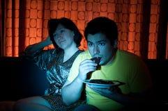 Junge Paare, die einen Film auf Fernsehapparat überwachen. Lizenzfreies Stockfoto