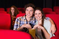 Junge Paare, die einen Film aufpassen stockfotografie