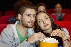 Junge Paare, die einen Film aufpassen Stockbild