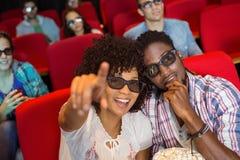 Junge Paare, die einen Film 3d aufpassen Stockbild