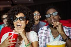 Junge Paare, die einen Film 3d aufpassen Stockfoto