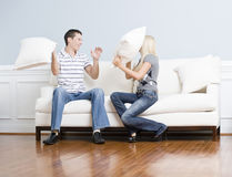 Junge Paare, die einen Kissen-Kampf auf Sofa haben Lizenzfreies Stockbild