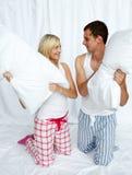 Junge Paare, die einen Kissenkampf haben stockfoto