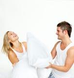 Junge Paare, die einen Kissenkampf mit Exemplarplatz haben Stockfotografie