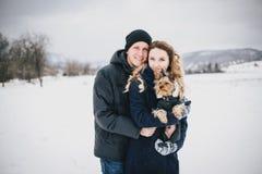 Junge Paare, die einen Weg mit ihrem Hund in der schneebedeckten Landschaft haben Stockfotografie