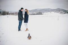 Junge Paare, die einen Weg mit ihrem Hund in der schneebedeckten Landschaft haben Lizenzfreies Stockfoto