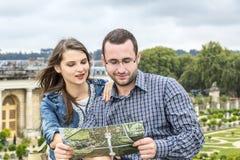 Junge Paare, die in einer Karte schauen Stockfotos