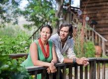Junge Paare, die an einer kleinen Brücke in einem Garten stillstehen Stockbild