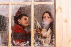 Junge Paare, die in einer Winterkabine feiern Stockbild