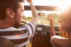 Junge Paare, die entlang Land-Straße im offenen Auto fahren Stockfoto