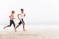 Junge Paare, die entlang Winter-Strand laufen stockbild