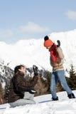 Junge Paare, die Fotos auf dem Schnee nehmen Stockfoto