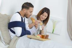 Junge Paare, die Frühstück auf Bett essen lizenzfreie stockbilder