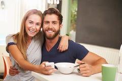 Junge Paare, die Frühstück essen, während, Handys verwendend stockbild