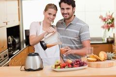 Junge Paare, die Fruchtsaft machen Stockbilder