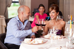 Junge Paare, die Gaststättetabelle rösten lizenzfreie stockfotos
