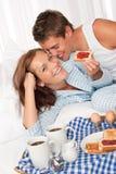 Junge Paare, die gebildetes Haupt im Bett frühstücken lizenzfreie stockbilder