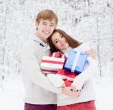 Junge Paare, die Geschenke umarmen und halten stockfotografie