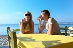 Junge Paare, die Getränke an der Küste genießen Stockbild