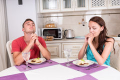 Junge Paare, die Grace Before Eating Meal sagen Stockfoto