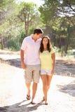 Junge Paare, die Hände, gehend anhalten, gehen in Park Lizenzfreies Stockfoto
