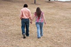 Junge Paare, die Hand in Hand gehen Stockfotos