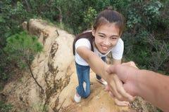 Junge Paare, die, Handreichung, Wandererfrau erhält Hilfe auf lächelndem glücklichem Überwindungshindernis der Wanderung, tourist lizenzfreie stockfotografie