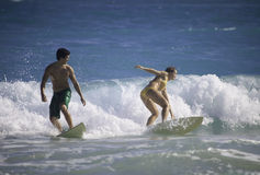 Junge Paare, die in Hawaii surfen Lizenzfreies Stockfoto