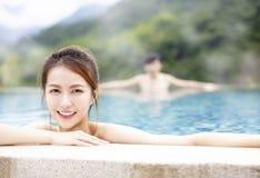 Junge Paare, die in heiße Quellen sich entspannen lizenzfreie stockfotografie