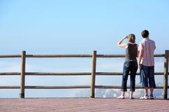 Junge Paare, die heraus zum Meer von der hohen Veranschaulichung schauen stockfotografie