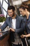 Junge Paare, die herein an der Hotelaufnahme überprüfen Lizenzfreie Stockfotos