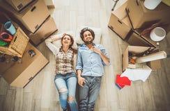 Junge Paare, die herein in neue Wohnung sich bewegen Stockbild