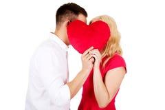 Junge Paare, die hinter dem Kissen flüstern Lizenzfreie Stockfotos