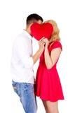 Junge Paare, die hinter dem Kissen flüstern Lizenzfreies Stockfoto