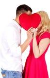 Junge Paare, die hinter dem Kissen flüstern Lizenzfreies Stockbild