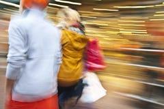 Junge Paare, die hinunter Einkaufsstraße gehen Stockbild