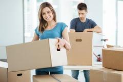 Junge Paare, die in ihr neues Haus sich bewegen Lizenzfreies Stockbild