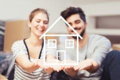 Junge Paare, die ihr neues, Traumhaus in den Händen halten lizenzfreie stockfotos