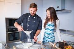 Junge Paare, die in ihre Küche, Konzept des Kochens, Familie sich vorbereiten lizenzfreie stockfotografie
