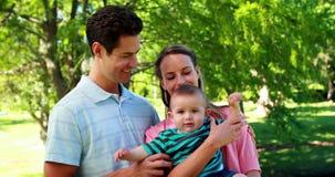 Junge Paare, die ihren Babysohn lächelt an der Kamera im Park halten stock video