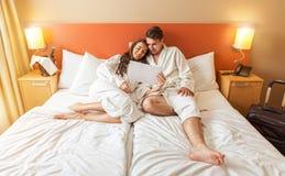 Junge Paare, die im Bett eines Hotelzimmers liegen Stockbilder
