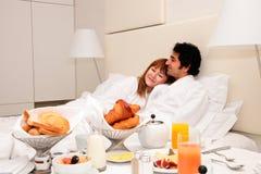 Junge Paare, die im Bett frühstücken Stockbild