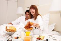 Junge Paare, die im Bett frühstücken Lizenzfreie Stockfotos