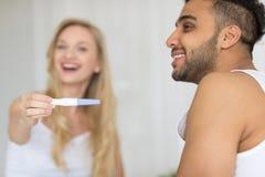 Junge Paare, die im Bett, glückliche Lächeln-Frauen-Show aufgeregter überraschter Mann-Positiv-Schwangerschaftstest sitzen stockbilder